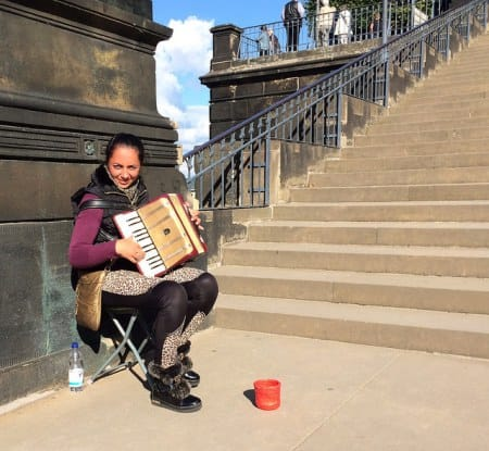 An accordionist, with her chair and money jar, waits for passers-by to listen and donate a Euro or two near a Dresden viewpoint along the Elba River.