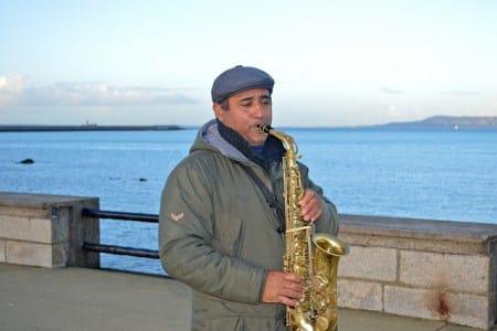 A saxophonist blows a melancholy tune near Sandycove outside Dublin.