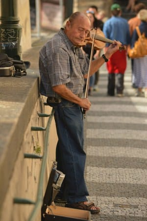 A fiddler leans against a wall leading up to the Prague Castle. He plays there often.