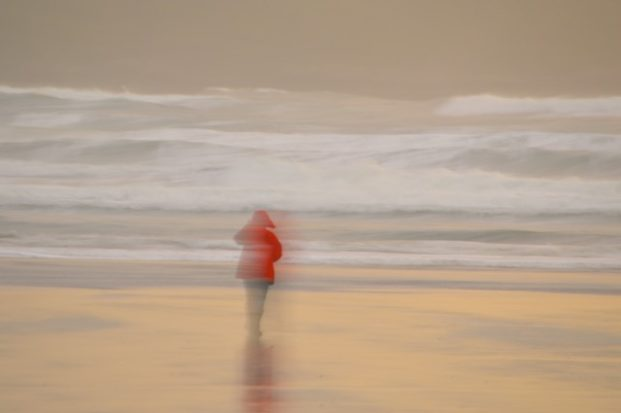 Woman in red jacket in a storm, at the beach