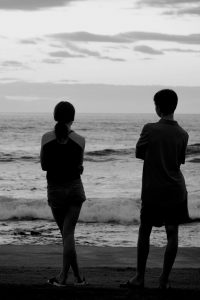 Black and white photograph of two young people standing next to each other, silhouetted against the beach and sky