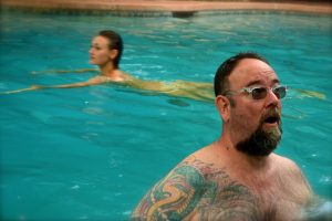 Two people swimming in a pool, a tattooed man looking surprised in the foreground and a nude woman swimming behind him