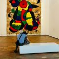 A man and woman embrace while sitting on a bench in a gallery, looking onto a large woven piece of art in the style of Jean Miro