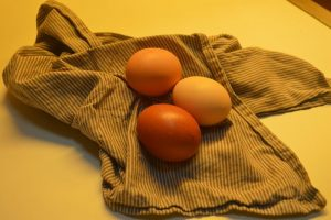 Three eggs placed on a striped dish towel