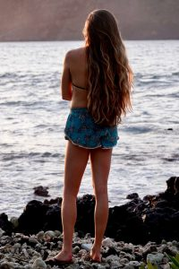 A young woman with long wavy hair looks out over lake from a rocky shore
