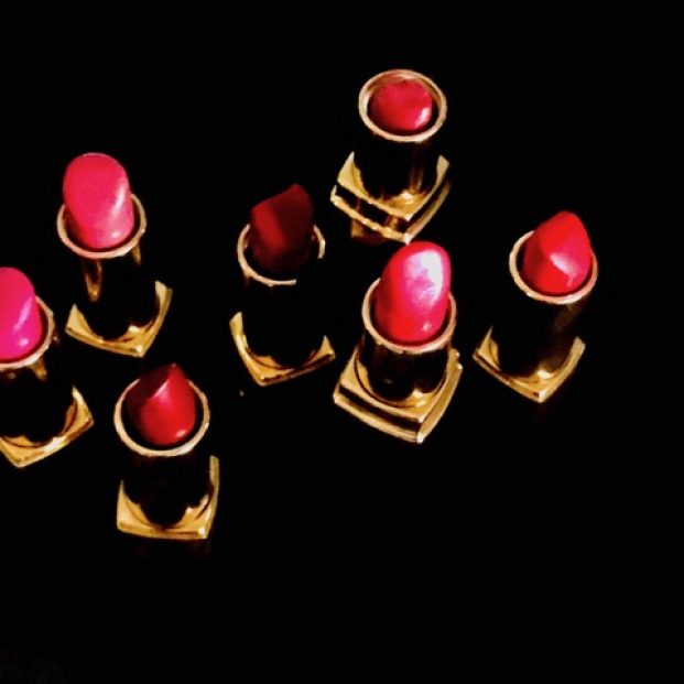 Seven open lipsticks, in various shades of pink and red, in gold cases, photographed from above against a black background.