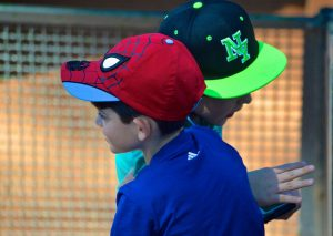 Two boys in baseball caps outside