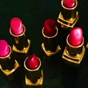 Six open lipsticks, in various shades of pink and red, in gold cases, photographed from above against a black background.
